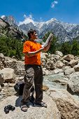 image of himachal pradesh  - Hiker trekker studying map route on trek in Himalayas mountains - JPG