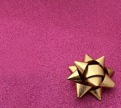 foto of girly  - Pink shimmer sparkle background with a gold gift wrap bow - JPG