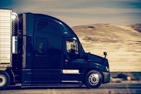 picture of trucks  - Speeding Dark Blue Semi Truck in Nevada United States - JPG
