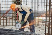 image of millwright  - Construction builder worker with grinder machine cutting metal reinforcement rebar rods at building site - JPG