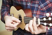 foto of ukulele  - Close Up Of Man Playing Ukulele At Home - JPG