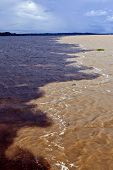 foto of negro  - Meeting of the waters sandy colored Rio Solimoes and almost black Rio Negro near Manaus in Amazon - JPG