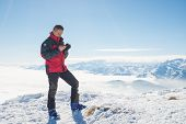 pic of italian alps  - Alpinist with phone in hand on the summit with majestic panoramic view of the italian Alps in winter season - JPG