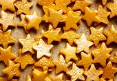 picture of sprinkling  - Colorful sweet background with gold star sprinkles close up on craft paper - JPG