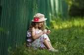 image of girlie  - Little girl sits leaning against a fence - JPG