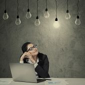 picture of lightbulb  - Portrait of young businesswoman working on tablet while looking at lightbulb - JPG