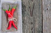 stock photo of chillies  - Chilli pepper on linen texture and wooden table - JPG