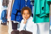 picture of clothes hanger  - African boy in white shirt with hand on cheek sitting under hangers with clothes after shopping in the clothes store - JPG