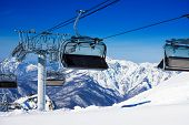 stock photo of ropeway  - View of ski lift chair on ropeway over mountains on background on winter ski resort - JPG
