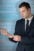 foto of cuff  - Businessman adjusting his cuffs on shirt against wooden planks - JPG