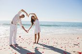 stock photo of shapes  - Loving couple forming heart shape with arms against red love hearts - JPG