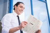 picture of unemployed people  - Smiling unemployed man in suit reading newpaper outdoors - JPG