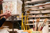 picture of pottery  - Work table of a pottery decorator of Caltagirone with different color containers and paintbrushes  - JPG