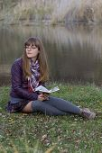 image of straight jacket  - young girl reading a book at the lake - JPG