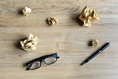 stock photo of stress-ball  - Crumpled paper balls with eye glasses and pen on wood desk creative writing concept - JPG