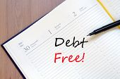 stock photo of debt free  - Yellow blank notepad on office wooden table Debt Free concept - JPG