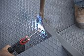 picture of welding  - Two men working over iron platform with arc welding - JPG