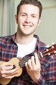 foto of ukulele  - Portrait Of Smiling Young Man Playing Ukulele - JPG