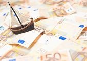 stock photo of fifties  - Tiny ship over the surface covered with the multiple fifty euro bank notes - JPG