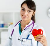 foto of heart surgery  - Beautiful smiling female doctor holding red heart in front of chest closeup - JPG