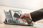 picture of telemarketing  - Closeup of a hand in a formal elegant suit dialing a telephone number on a classical black landline phone - JPG