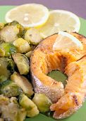 stock photo of brussels sprouts  - Steak of a trout with roasted brussels sprouts and lemon - JPG