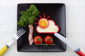 picture of black-cherry  - Bright happy breakfast with sunny egg bacon tree with parsley leaves and cherry tomato flowers on black square plate on white wood table - JPG