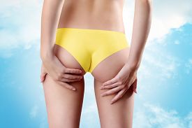 stock photo of bum  - Bum and legs of woman hands touching the buttocks over sky background - JPG