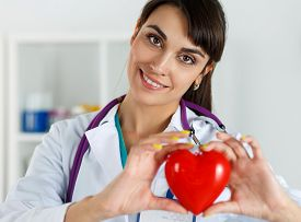 image of resuscitation  - Beautiful smiling female doctor holding red heart in front of chest closeup - JPG