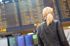 stock photo of check  - Casually dressed young stylish female traveller checking a departures board at the airport terminal hall in front of check in couters - JPG