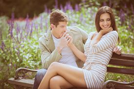 stock photo of sitting a bench  - Loving young couple flirting while sitting at a park bench - JPG