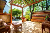 Backyard Deck With Wicker Furniture And Pergola. poster