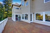 Two Story House With Wooden Walkout Deck Overlooking Backyard Garden. poster