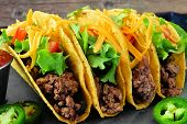 Group Of Hard Shelled Tacos With Ground Beef, Lettuce, Tomatoes And Cheese Close Up poster