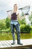 picture of fisherwomen  - fishing woman with landing net standing on pier - JPG