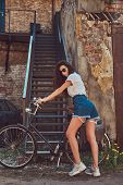 Cool Slim Girl In Short Denim Shorts, White T-shirt And Sunglasses, Posing With The City Bicycle Nea poster