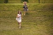 Girls Run From Hill On Green Grass On Summer Day On Natural Landscape. Energy, Energizer, Resilience poster