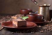 Chocolate Cake With Mint On A Brown Plate. Chocolate Cake On A Old Wooden Table With Coffee Beans. poster