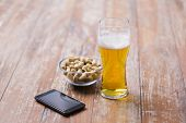 food and drinks concept - glass of draught beer, smartphone and pistachio nuts on table poster