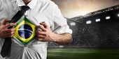 Brazil soccer or football supporter showing flag under his business shirt on stadium. poster