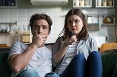 Scared Millennial Couple Watching Horror Movie On Tv Holding Remote Control At Home, Frightened Youn poster