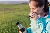 Atmosperic Photo Of The Young Female Traveller Is Drinking A Coffee From The Travel Metallic Cup In  poster