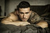 Shirtless Muscular Sexy Male Model Lying Alone On Bed In His Bedroom, Looking At Camera With A Seduc poster