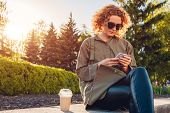 Attractive Young Girl Student With Curly Red Hair Having Coffee And Using Smartphone In Summer Park. poster
