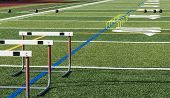 Athletic Turf Field Set Up For Speed, Strength And Agility Practice With Hurdles, Medicine Balls And poster