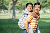 Loving Middle-aged Man Looking Away With Toothy Smile While Giving Piggyback Ride To Little Son, Pic poster