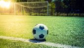 Soccer Sunset. Football In The Sunset. Closeup Soccer Ball On Green Grass At Sunset poster