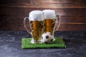 Photo Of Two Beer Mugs, Green Grass With Soccer Ball On Wooden Background poster