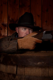 pic of wild west  - A cowboy hiding behind a barrel getting ready to shoot his rifle - JPG