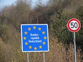 German Border On Small Road. Blue Board With Yellow Eu Stars, Bundesrepublik Deutschland Means Germa poster